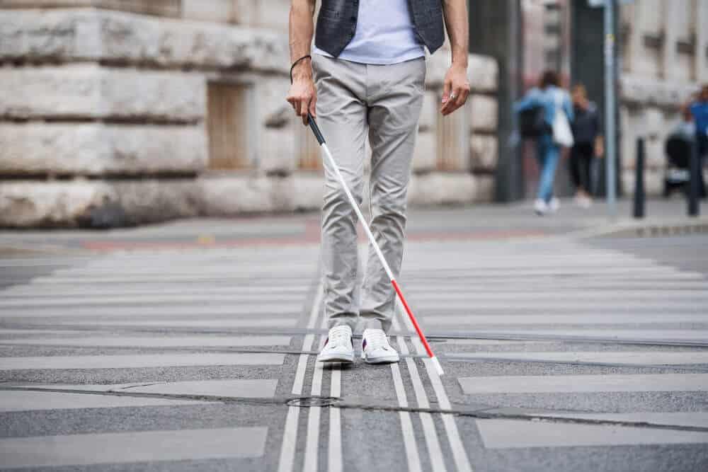 Mann mit Blindenstock auf der Straße